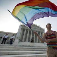 Gay rights advocate Vin Testa waves a rainbow flag in front of the Supreme Court at sun up  on Wednesday (J. Scott Applewhite/ AP)