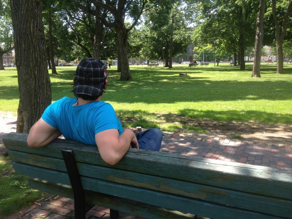 Frank, a 21-year-old homeless man, on his favorite Cambridge Commons bench. (Martha Bebinger/WBUR)