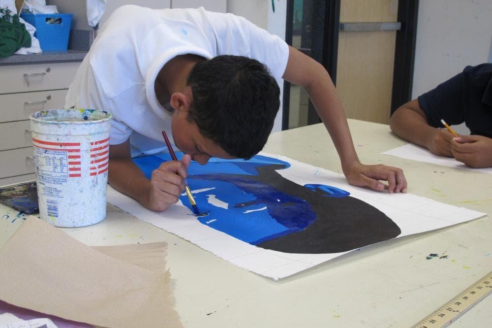 A student paints at Orchard Gardens School. (Ava Aguado/WBUR)