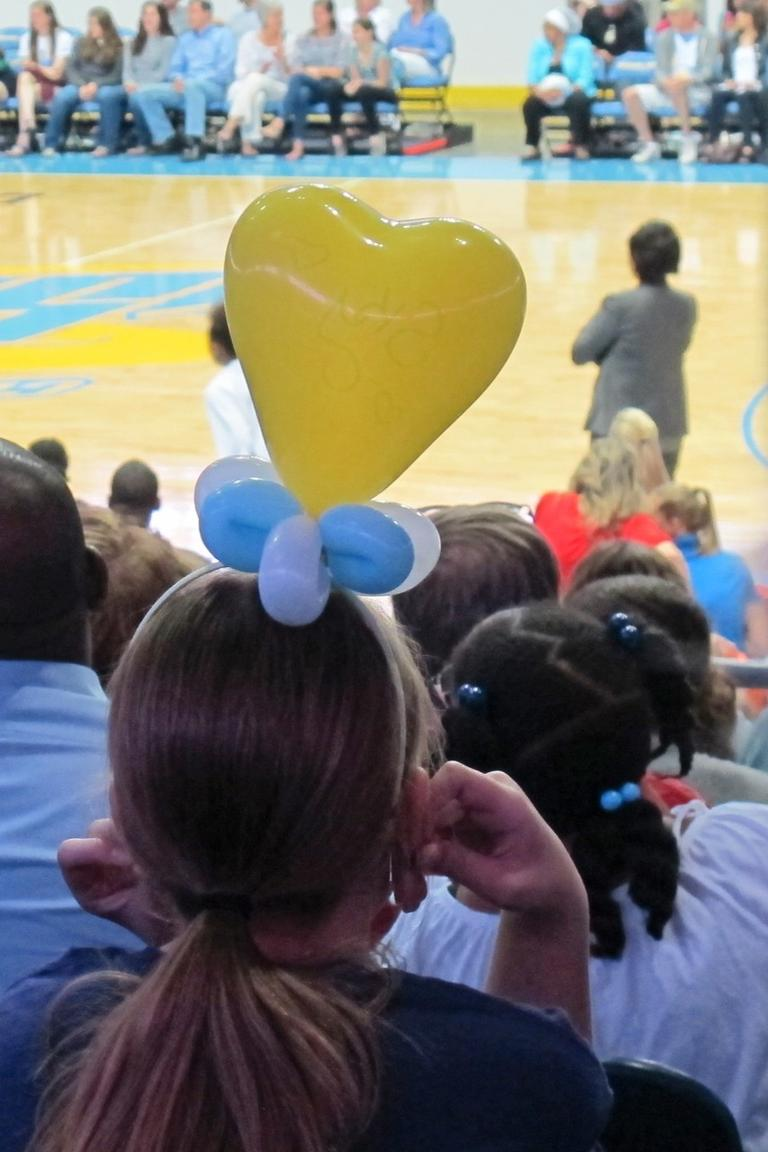 Kids in balloon hats sit on the near side of the stadium. (Only A Game/Karen Given)