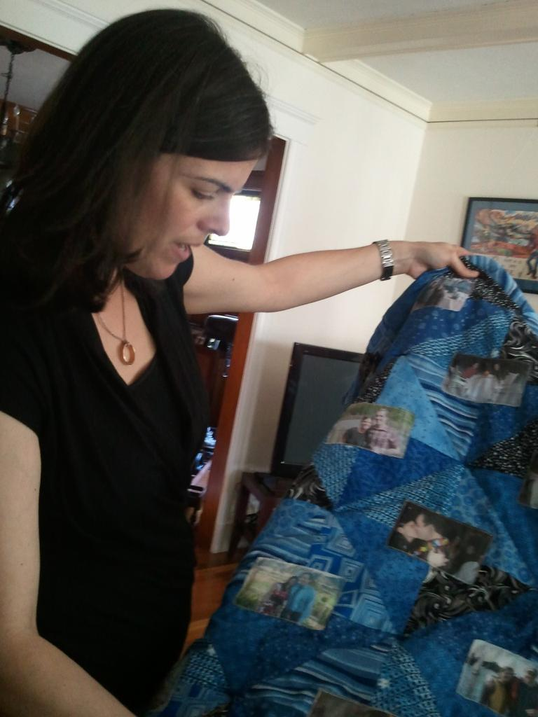 Sara Selig showing quilt made with photos of her late-husband Gregg Stracks (Courtesy)