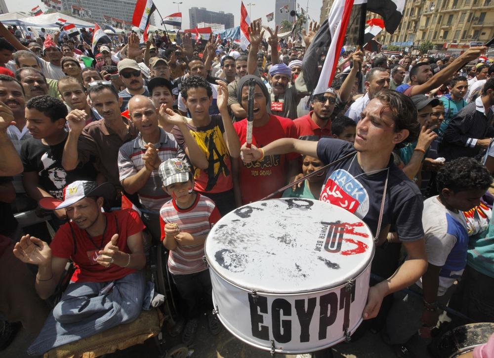 Egyptian protesters shout slogans and wave national flags during a demonstration against Egypt's Islamist President Mohammed Morsi in Tahrir Square in Cairo, Monday, July 1, 2013. (Amr Nabil/AP)