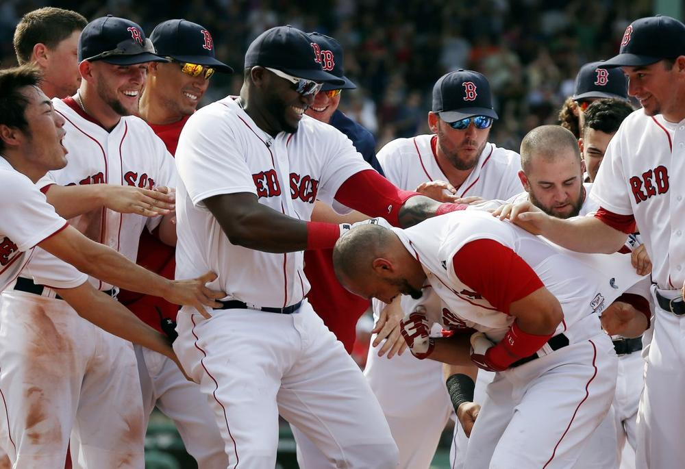 Teammates celebrate with Boston Red Sox's Shane Victorino, front second from right, after reaching on a fielding error allowing the Red Sox's Jonathan Diaz to score in the ninth inning of a baseball game against the Toronto Blue Jays. (Michael Dwyer/AP)