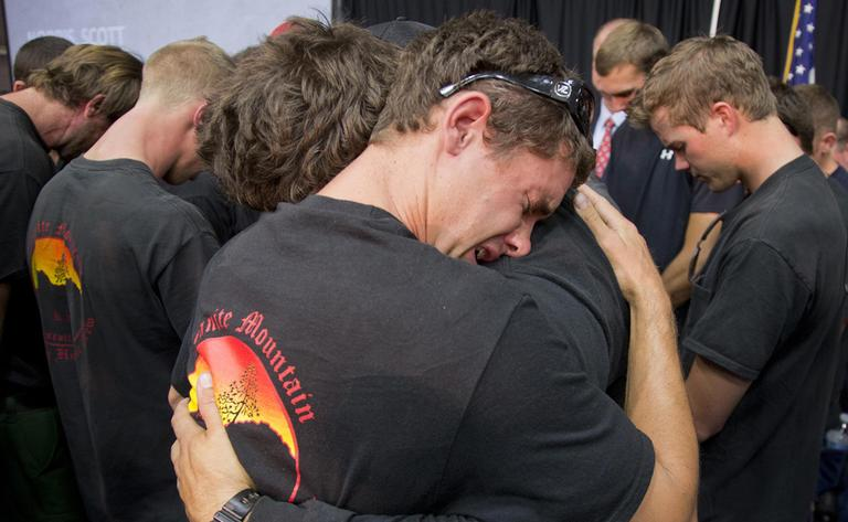 Prescott and other area department firefighters embrace during a memorial service, Monday, July 1, 2013 in Prescott, Ariz. for the 19 Granite Mountain Hotshot Crew firefighters who were killed Sunday, when an out-of-control blaze overtook the elite group. (Julie Jacobson/AP)