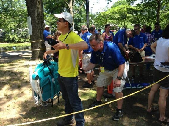 """Pictured here are people being """"wanded"""" at a Hatch Shell security checkpoint. One woman had plastic silverware confiscated. (Lynn Jolicoeur/WBUR)"""