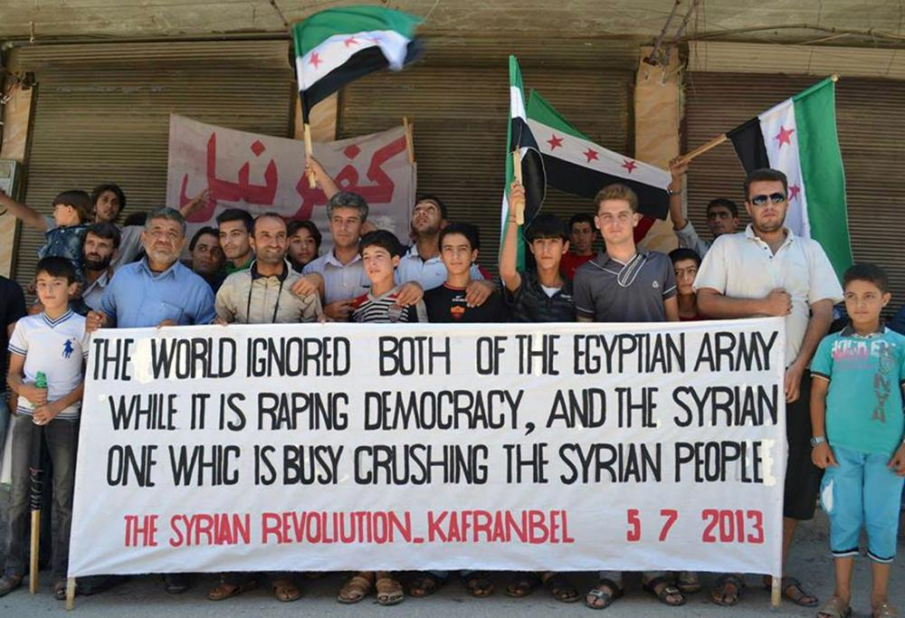 This citizen journalism image provided by Edlib News Network, ENN, shows anti-Syrian regime protesters holding a banner and Syrian revolution flags during a demonstration at Kafr Nabil town in Idlib province, northern Syria, Friday. (AP/Edlib News Network ENN)