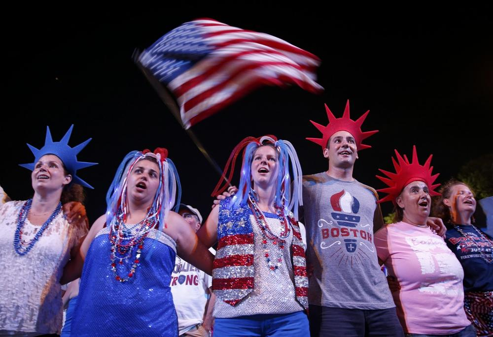 Audience members join arms as the Boston Pops play God Bless America during their Fourth of July Concert at the Hatch Shell in Boston, Thursday, July 4, 2013. (Michael Dwyer/AP)