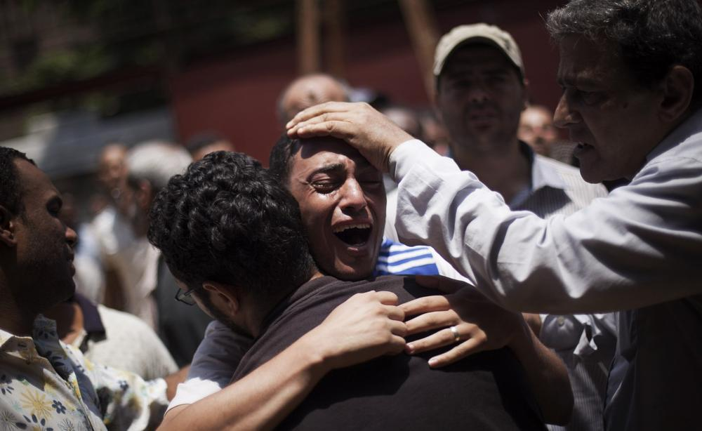 An Egyptian man cries outside a morgue after carrying the corpse of his brother killed near the Republican Guard building in Cairo, Egypt, Monday, July 8, 2013. (Manu Brabo/AP)