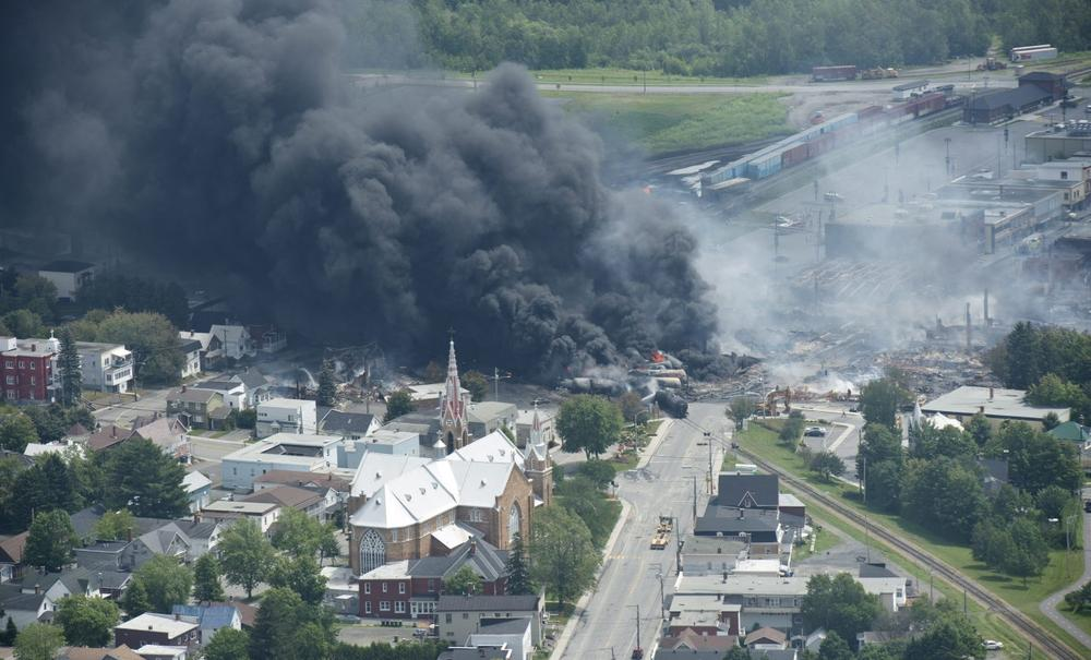 Smoke rises from railway cars that were carrying crude oil after derailing in downtown Lac Megantic, Quebec, Canada, Saturday, July 6, 2013. (Paul Chiasson/The Canadian Press via AP)