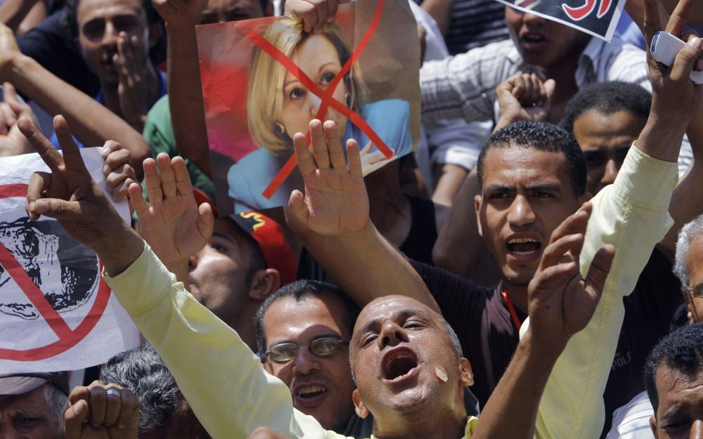 Egyptian protesters shout anti-Muslim brotherhood slogans as they hold posters depicting U.S. Ambassador to Egypt Anne Patterson and President Mohammed Morsi in Tahrir Square, the focal point of Egyptian uprising, in Cairo, Egypt, Friday, June 28, 2013. (Amr Nabil/AP)