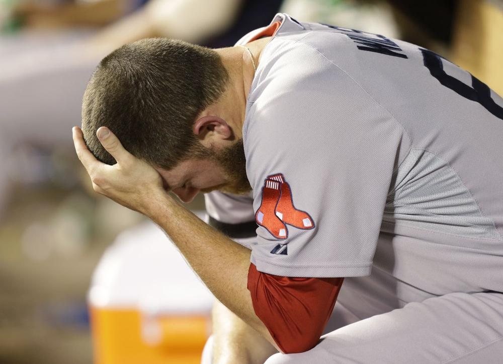 Red Sox pitcher Alex Wilson rests in the dugout after he was pulled from a baseball game against the Seattle Mariners. (Ted S. Warren/AP)