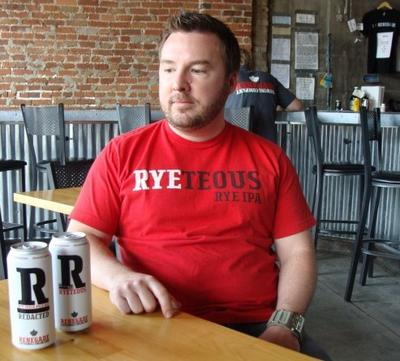 Brian O'Connell of Denver's Renegade Brewing shows off the new design for his renamed beer, Redacted. (Megan Verlee/Colorado Public Radio)