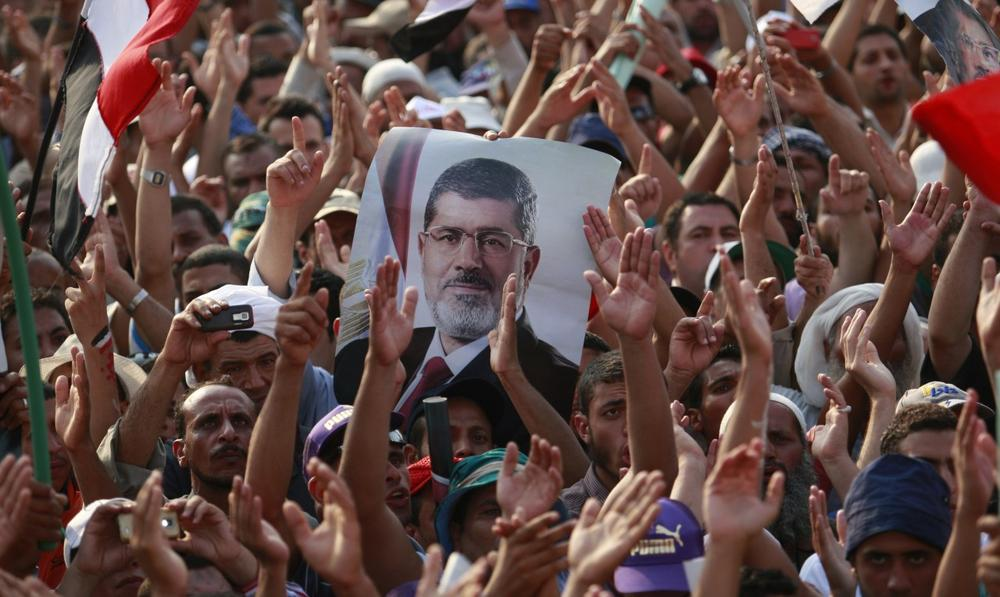 Supporters of ousted President Mohammed Morsi, seen in poster, protest in Nasr City, Cairo, Egypt, Tuesday, July 9, 2013. (Nasser Shiyoukhi/AP)