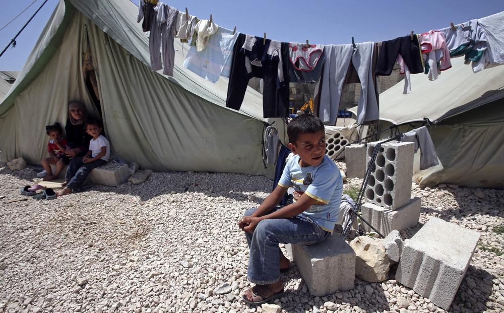 A Syrian refugee boy, right, sits outside his tent next to his family at a temporary refugee camp in the eastern Lebanese town of Marj near the border with Syria, Lebanon, Monday, May 20, 2013. (Hussein Malla/AP)