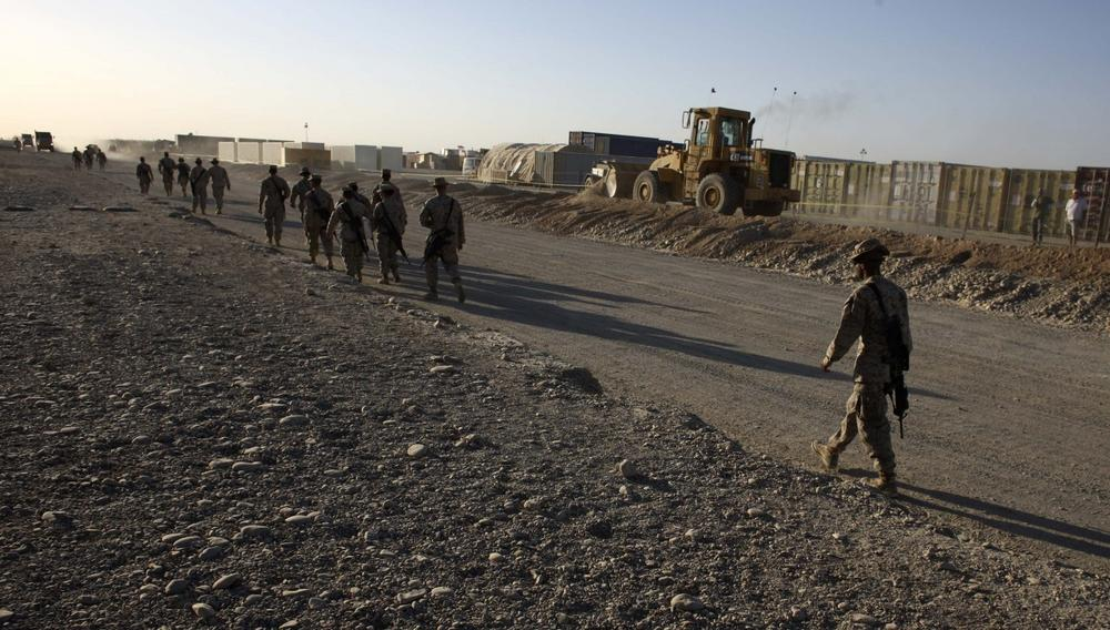 U.S. Marines walk past heavy machinery and containers where construction is taking place inside Camp Leatherneck, in Helmand province, southern Afghanistan, Oct. 9, 2009. (Brennan Linsley/AP)