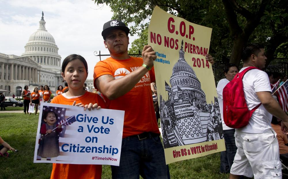 Brian Rossell, and his daughter Kelly Rossell, 11, both from Sonsonate, El Salvador, hold up placards as they join immigration supporters during a rally for citizenship on Capitol Hill in in Washington, Wednesday, July 10, 2013, coinciding with the GOP House Caucus meeting. (Manuel Balce Ceneta/AP)