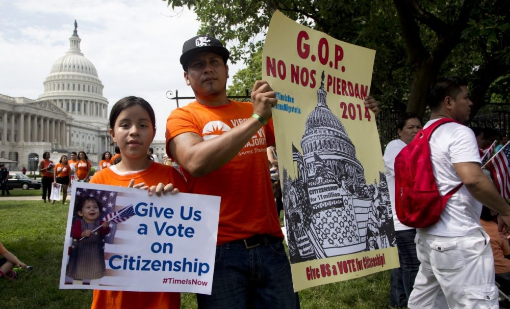 Brian Rossell, and his daughter Kelly Rossell, 11, both from Sonsonate, El Salvador, hold up placards as they join immigration supporters during a rally for citizenship on Capitol Hill in Washington, July 10, 2013. (Manuel Balce Ceneta/AP)