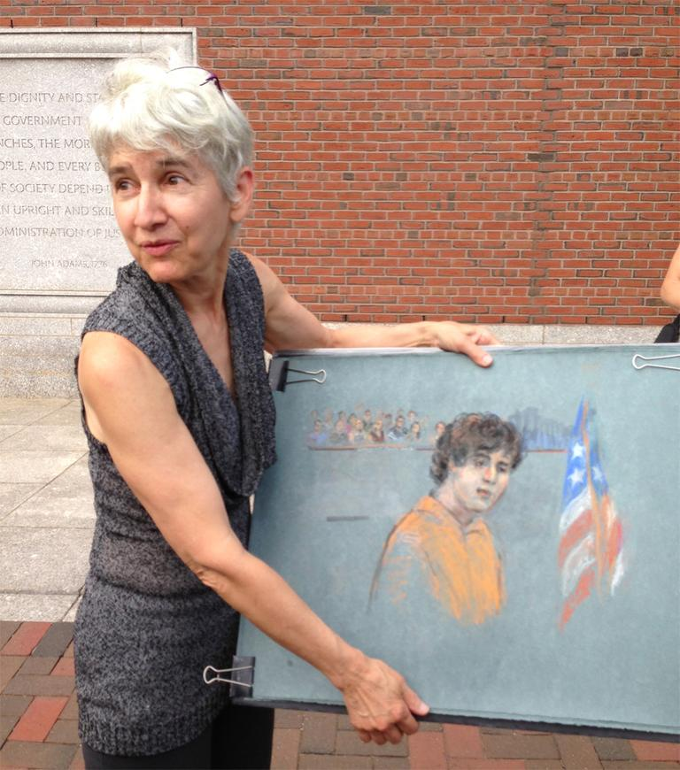 Courtroom sketch artist Margaret Small holding her sketch of alleged Boston Marathon bomber Dzhokhar Tsarnaev. (Bruce Gellerman/WBUR)