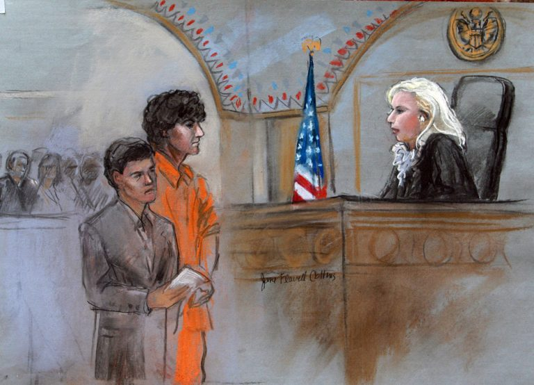 This courtroom sketch depicts bombing suspect Dzhokhar Tsarnaev standing with his lawyer Miriam Conrad, left, during his arraignment Wednesday. (Jane Flavell Collins/AP)