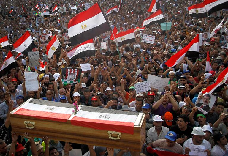 Supporters of ousted President Mohammed Morsi hold up a symbolic coffin, representing some 51 people killed Monday, in Nasr City, Cairo, Egypt, Tuesday, July 9, 2013. (AP)