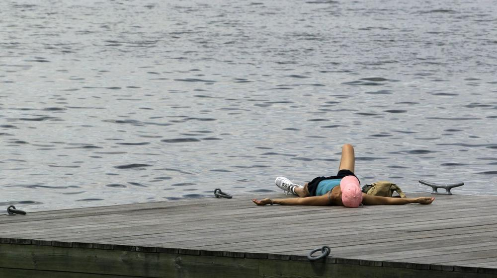 A sunbather relaxes on a dock along the Charles River, where the first public swim in over 50 years was held. (Elise Amendola/AP)