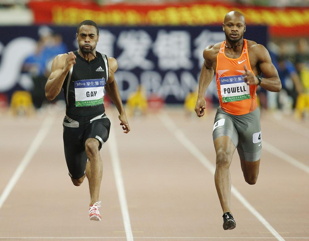Tyson Gay of the United States, left, and Asafa Powell of Jamaica, right, during their 100 meter race at the 2009 Shanghai Golden Grand Prix. (Eugene Hoshiko/AP)