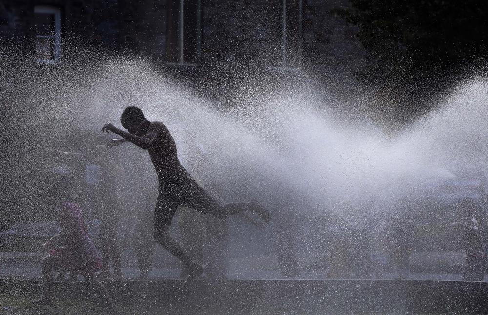 Kids cool off in the spray of an open hydrant on a hot evening in Lawrence, Mass. Tuesday, July 16, 2013. (Elise Amendola/AP)