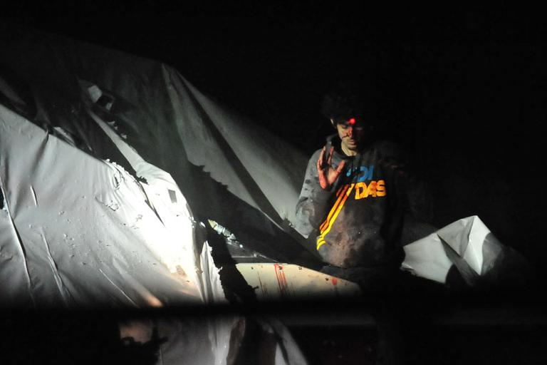 Alleged marathon bomber Dzhokhar Tsarnaev emerges from a boat during his capture. (Courtesy Sgt. Sean Murphy, via Boston Magazine)