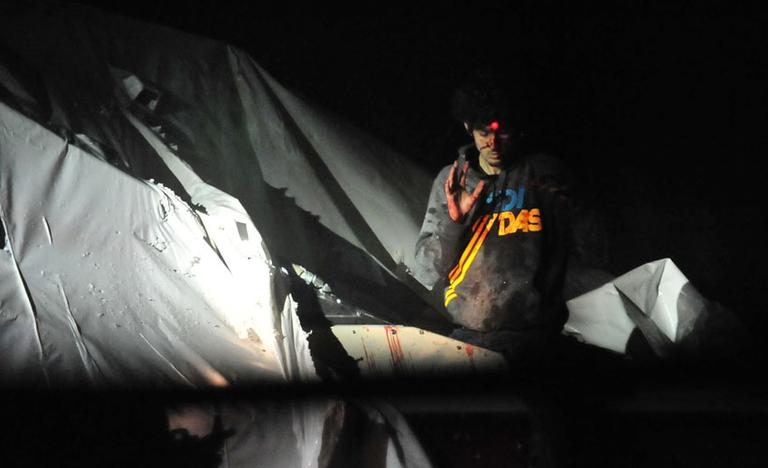 Alleged marathon bomber Dzhokhar Tsarnaev emerges from a boat in Watertown as he is captured. (Courtesy Sgt. Sean Murphy, via Boston Magazine)