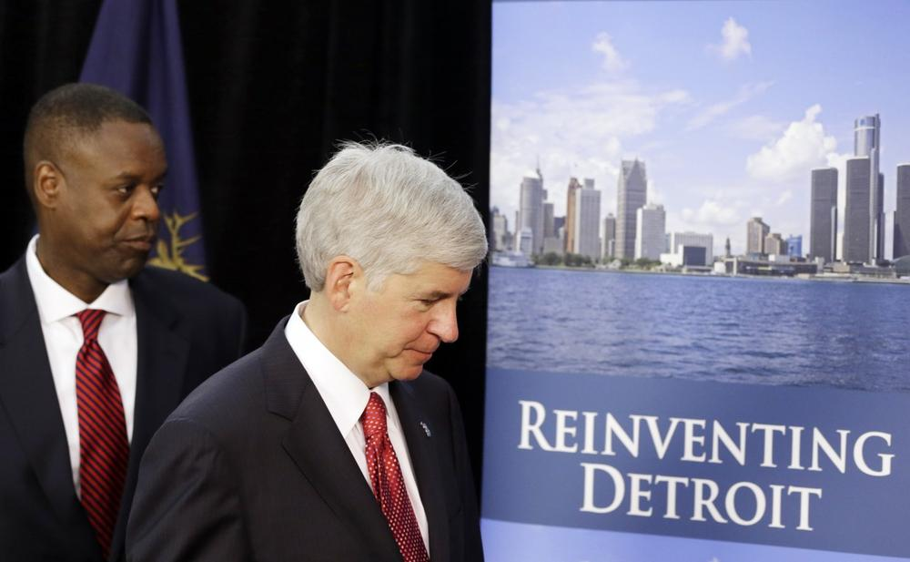 Michigan Gov. Rick Snyder, right, and state-appointed emergency manager Kevyn Orr leave a news conference in Detroit after addressing the city's bankruptcy, July 19, 2013. (Carlos Osorio/AP)