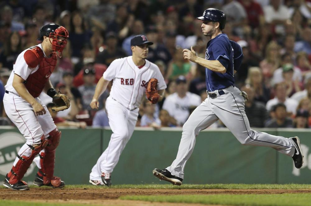 Tampa Bay Rays' Matt Joyce, right, scores on a sacrifice by Desmond Jennings during the ninth inning. (AP/Charles Krupa)