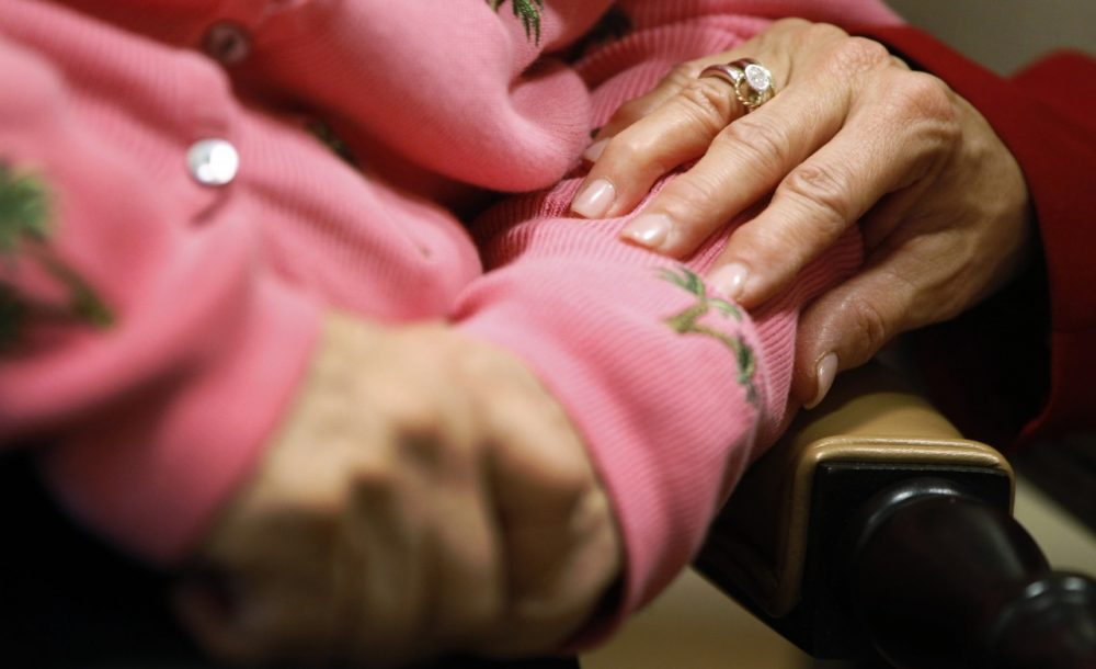 Alexis McKenzie, right, executive director of The Methodist Home of the District of Columbia Forest Side, an Alzheimer's assisted-living facility, puts her hand on the arm of resident Catherine Peake, in Washington, Feb. 6, 2012. (Charles Dharapak/AP)