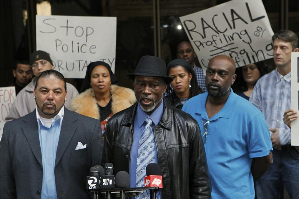Oscar Grant's uncles: Cephus Johnson, middle, at podium, and Kenneth Johnson, right, outside the Los Angeles Superior Court on Dec. 3, 2010. At left is Jack Bryson. (Damian Dovarganes/AP)