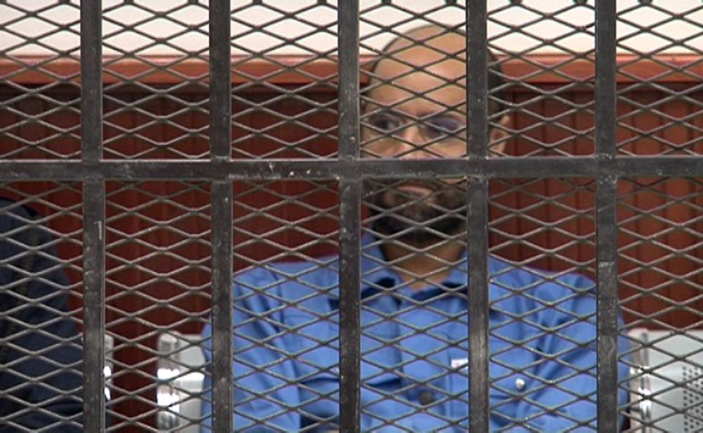 This image made from video distributed by the Zintan Media Center shows Seif al-Islam Gadhafi, center, inside a defendant's cage in a courtroom in Zintan, Libya, Thursday, May 2, 2013. (Zintan Media Center via AP)