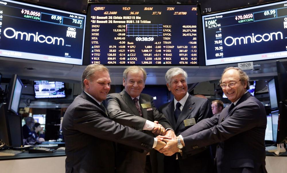 Omnicom Group CFO Randall Weisenburger, left, and President and CEO John Wren, second left, join hands with Publicis Groupe Chairman and CEO Maurice Levy, third left, and CFO Jean-Michel Etienne as they pose for photos on the floor of the New York Stock Exchange Monday, July 29, 2013. (Richard Drew/AP)