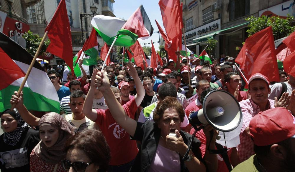 Palestinians wave national and PFLP (Popular Front for the Liberation of Palestine) flags in the West Bank city of Ramallah, during a protest against resuming peace talks with Israel, Sunday, July 28, 2013. (Majdi Mohammed/AP)