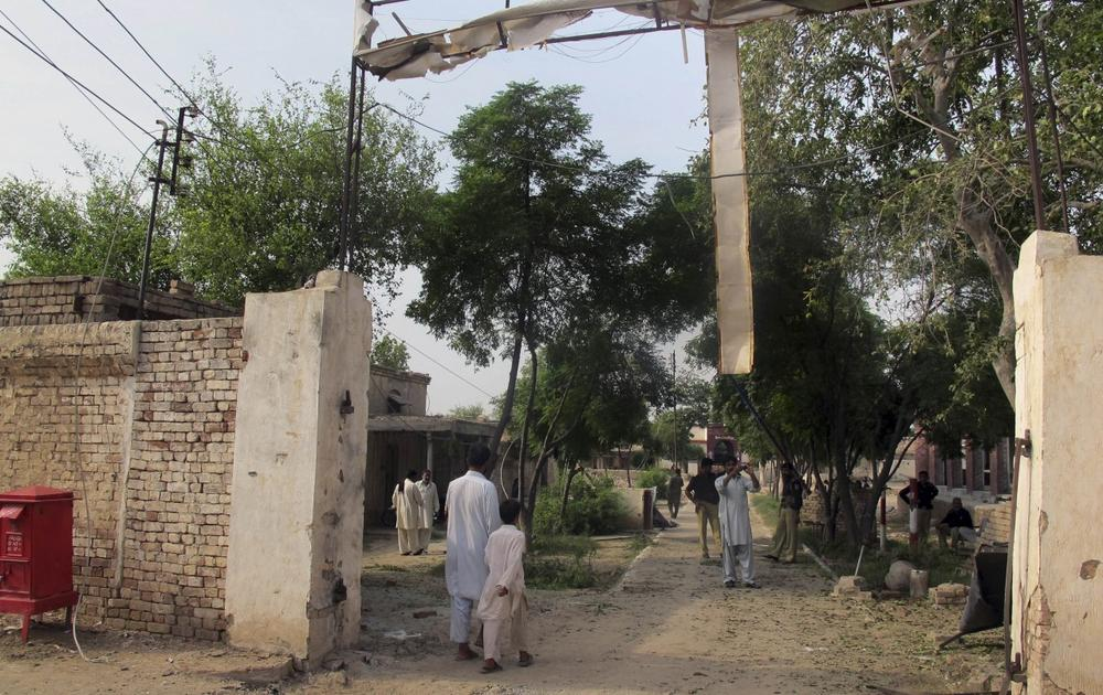 A plainclothes police officer takes a photo of a jail gate damaged in an attack by Taliban militants, Tuesday, July 30, 2013 in Dera Ismail Khan, Pakistan. (Ishtiaq Mahsud/AP)