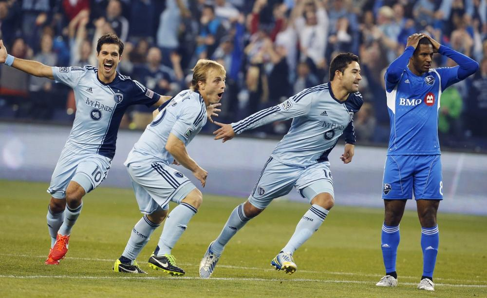 Sporting KC players Benny Feilhaber (10) and Seth Sinovic (15) celebrate a goal by Claudio Bieler (16), next to Montreal Impact midfielder Patrice Bernier (8) during the first half of an MLS soccer match in Kansas City, Kan., March 30, 2013. (Orlin Wagner/AP)