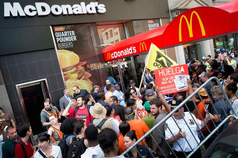 Demonstrators in support of fast food workers protest outside a McDonald's as they demand higher wages and the right to form a union without retaliation Monday, July 29, 2013, in New York's Union Square. (John Minchillo/AP)