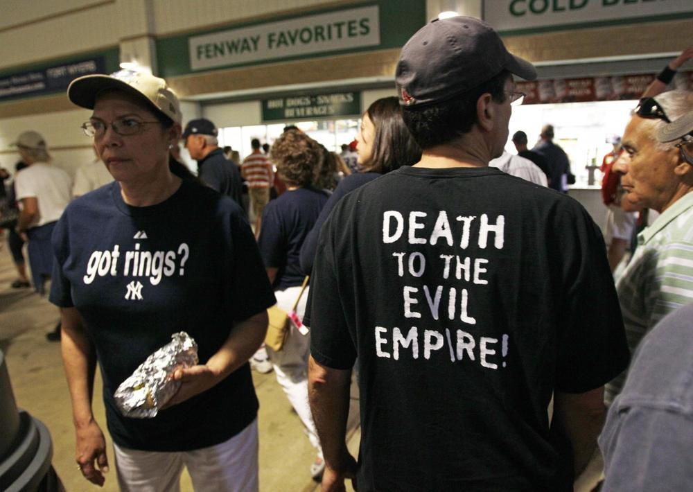 A Red Sox fan, right, passes a Yankees fan, left, at the concession stands at a spring training baseball game in Fort Myers, Fla., Monday, March 14, 2011. (Charles Krupa/AP)