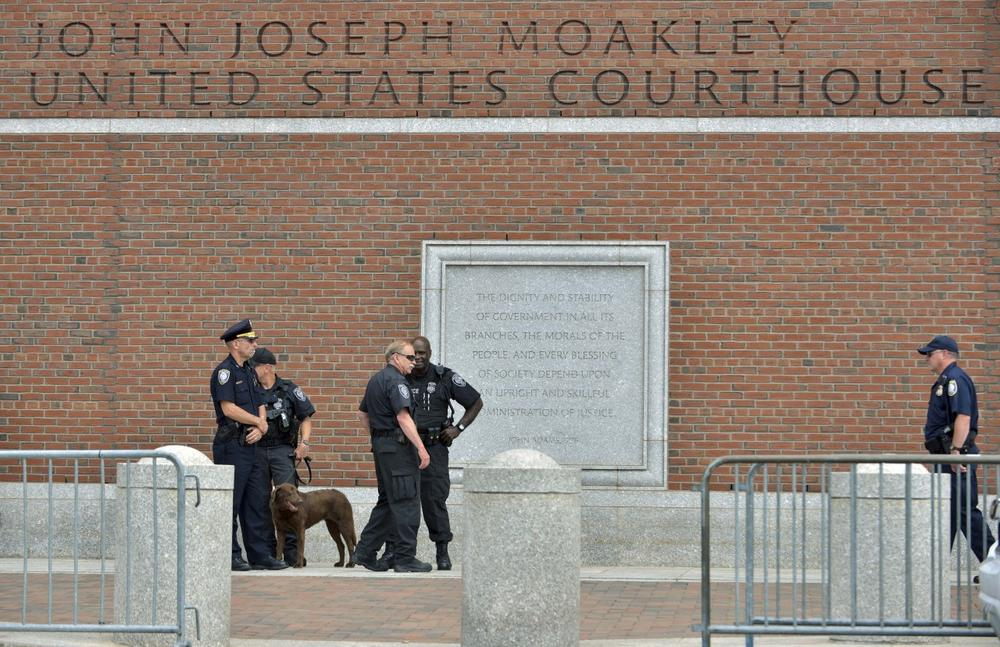 Federal law enforcement officers stand outside the federal courthouse prior to arraignment for Boston Marathon bombing suspect Dzhokhar Tsarnaev Wednesday, July 10, 2013, in Boston. The April 15 attack killed three and wounded more than 260. The 19-year-old Tsarnaev has been charged with using a weapon of mass destruction, and could face the death penalty.(AP Photo/Josh Reynolds)