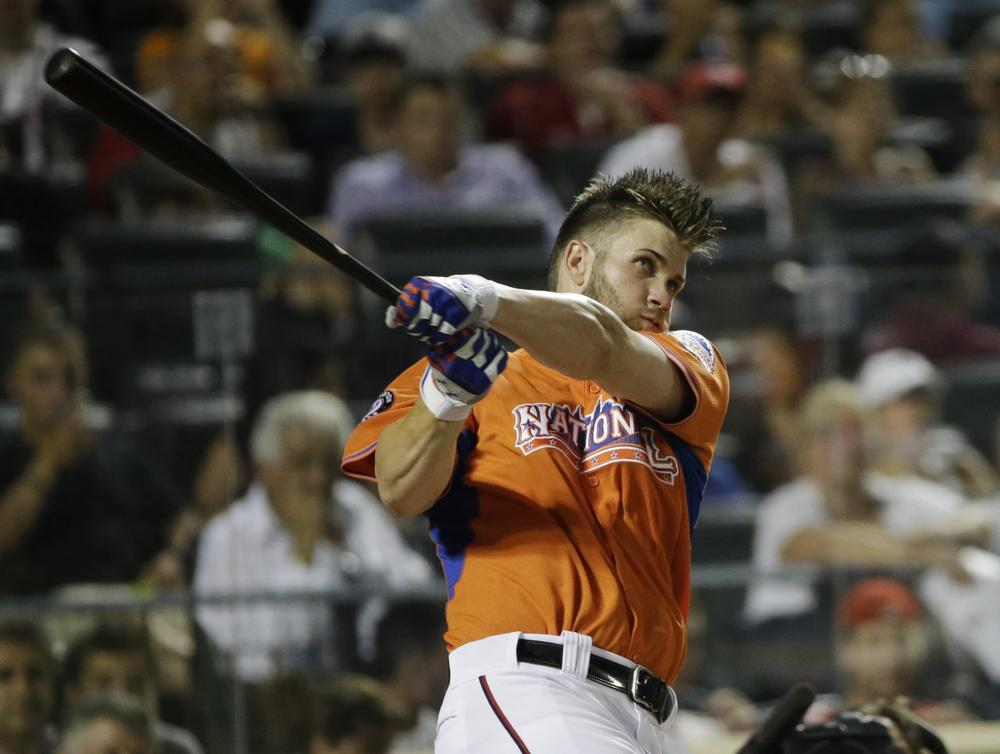 National League's Bryce Harper, of the Washington Nationals, watches his first home run in the third round of the MLB All-Star baseball Home Run Derby, on Monday, July 15, 2013 in New York. (AP)