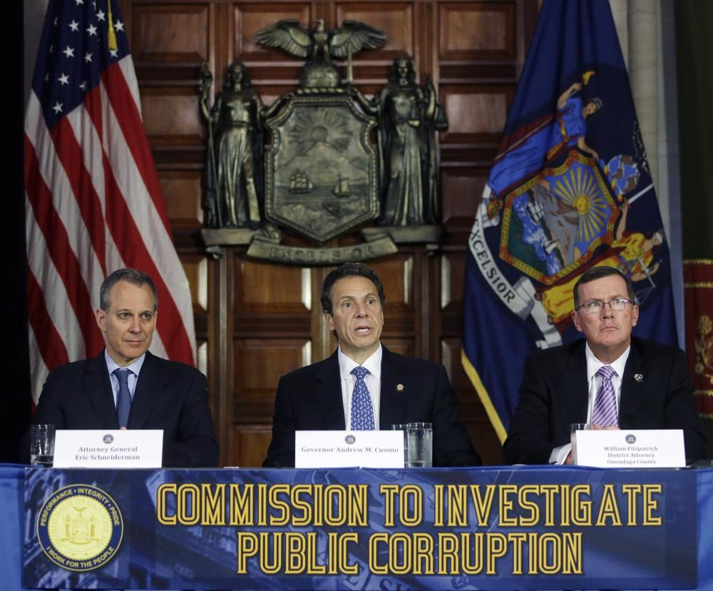 New York Gov. Andrew Cuomo, center, speaks during a news conference as New York Attorney General Eric Schneiderman, left, and Onondaga County District Attorney William Fitzpatrick listen on Tuesday, July 2, 2013, in Albany, N.Y. Cuomo has established a powerful investigative body to examine the state Board of Elections and potential wrongdoing by legislators in campaign fundraising. (AP/Mike Groll)