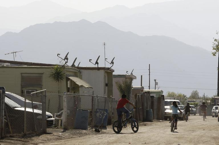 "Children riding bikes at the desert mobile home park called ""Duroville"" in Thermal, Calif. After a decade of legal wrangling, the encampment known as Duroville was scheduled to close Sunday June 30, 2013, by court order. (AP)"