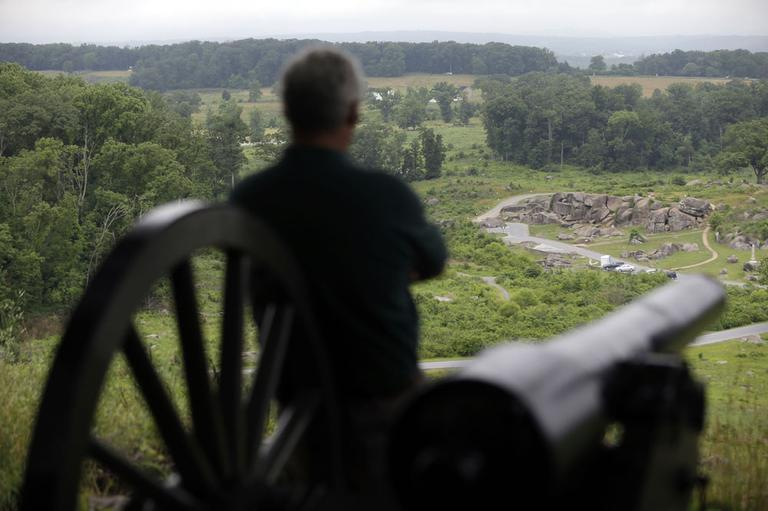 A visitor to Little Round Top views the Devil's Den during ongoing activities commemorating the 150th anniversary of the Battle of Gettysburg, Monday, July 1, 2013, in Gettysburg, PA. (AP)