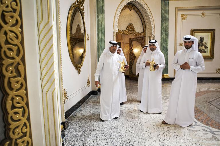 Men wait to serve tea to U.S. Secretary of State John Kerry, unseen, and Qatari Emir Hamad bin Khalifa Al Thani, unseen, during their meeting at Wajbah Palace in Doha, Qatar, on Sunday, June 23, 2013. (AP)
