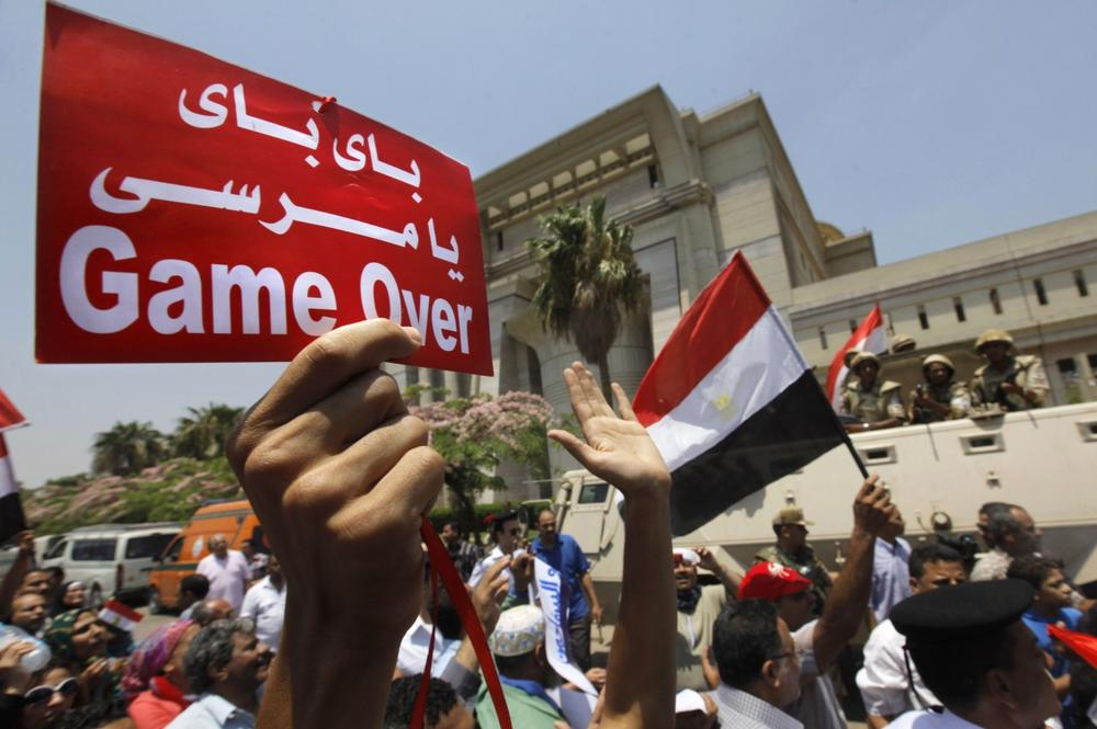 "Egyptians celebrate in front of the constitutional court after Egypt's chief justice Adly Mansour was sworn in as the nation's interim president Thursday, July 4, 2013. Arabic reads, "" bye bye Morsi."" (AP)"