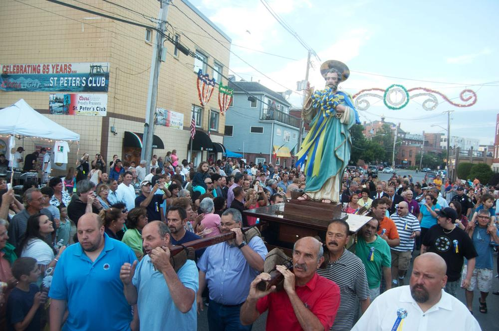 A crowd fills Rogers Street on Friday evening to watch the opening procession of the statue of St. Peter from the St. Peter's Club to the temporary outdoor altar on the waterfront in St. Peter's Square. (Greg Cook)