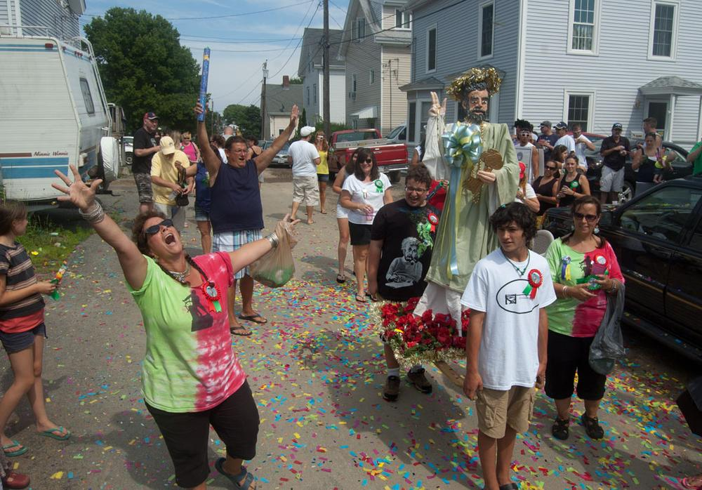 Three years ago Robyn McNair (left) and her sister Amy Clayton (in matching shirt at right) began holding a mini, tribute reenactment of the St. Peter's Fiesta during the festival weekend. McNair shouts blessings as her son Noah McNair (in black shirt) and nephew Jacob Belcher carry their replica St. Peter statue down Orchard Street. (Greg Cook)