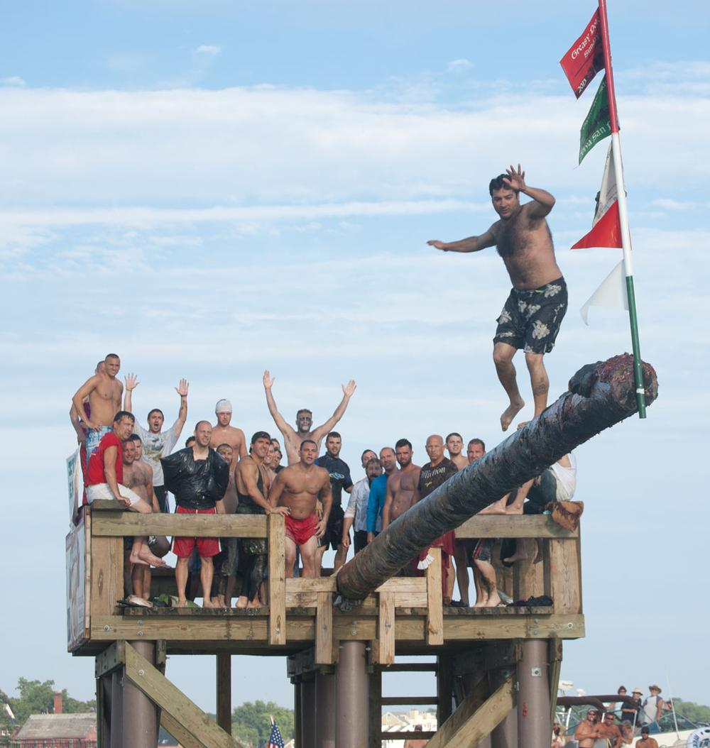 Nick Avelis, who won the Greasy Pole contest during the Saturday competition in 2012, steps carefully to the end to win again yesterday. (Greg Cook)